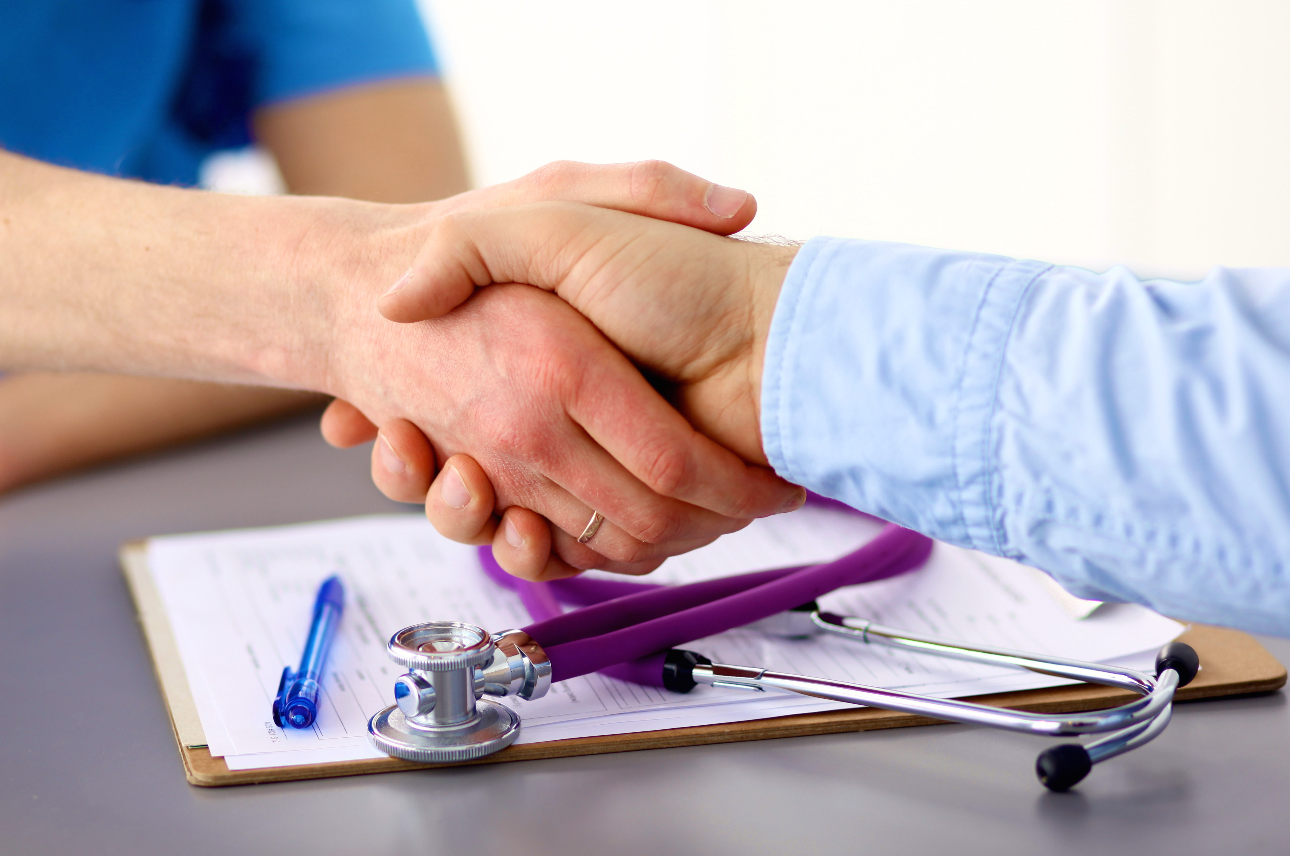 Doctor shakes hands with a patient isolated on white background .